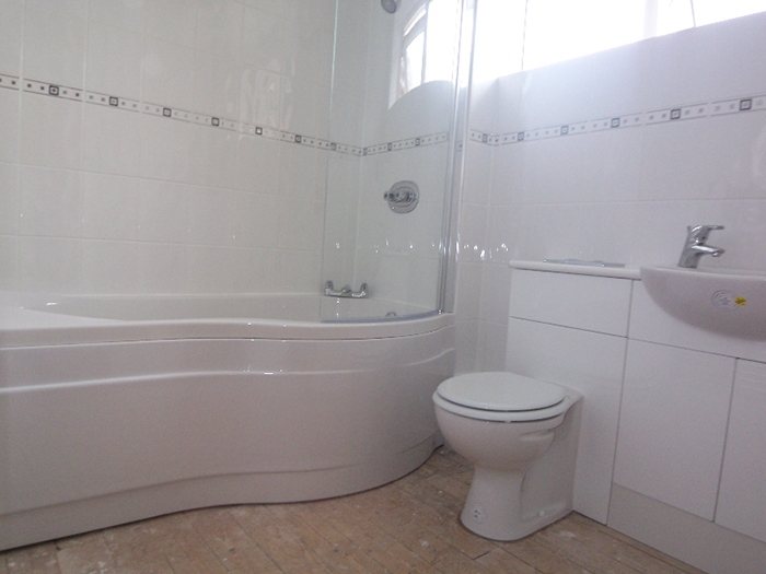 White bathroom with curved bath